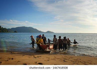 "a group of fishermen attract trawlers on the bungus beach in Padang. ""Maelo Pukek"". Padang, West Sumatra Indonesia. April 24, 2009"