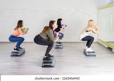 group of Fit Attractive women exercising with dumbbells in fitness club in aerobics class. Sport, yoga, healthy lifestyle