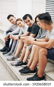 Group of fit friends sitting on steps and discussing half marathon they are preparing for