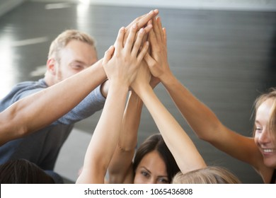 Group of fit happy people giving high five in fitness studio room, talking in a circle after seminar training. Setting goal, achieving team results. Teamwork, mindfulness, active life benefits concept