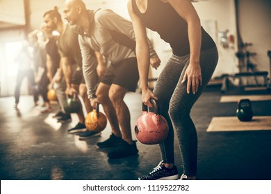 Group of fit people in exercise gear standing in a row lifting dumbbells during an exercise class at the gym