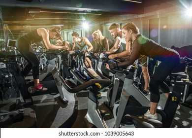Group of fit women and men riding exercise bikes at the gym.