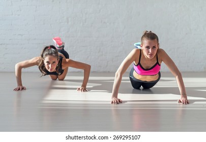 Group of fit women warming up and doing push ups working at gym fitness, sport, training, diet and lifestyle concept.
