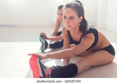 Group of fit women working stretching leg muscles of back to warm up at gym fitness, sport, training and lifestyle concept