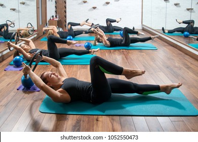 Group of fitness girls exercising with pilates rings in health club