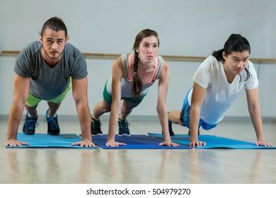 Group of fitness team doing push ups in fitness studio