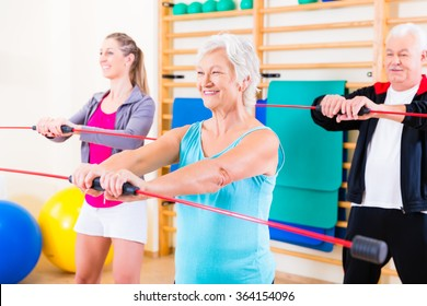 Group at fitness training with gymnastic bar, young and senior people exercising