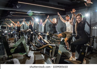 Group of fitness young women and men holding hands together and celebrating progress after successful cycling class in the gym.