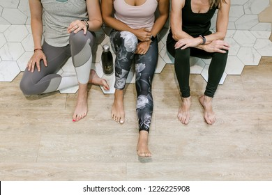 Group of five (5) women at pilates class demonstrating team work collaboration in light, airy fitness studio