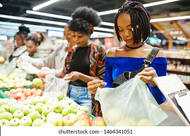 Group of five african womans picking up apples in plastic bags at supermarket.
