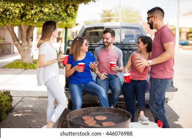 Group of five attractive friends talking about a football game over drinks during a hamburger barbecue