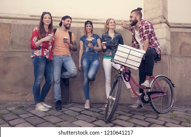 group of five cheerful best friends in the street having fun enjoy their lifestyle drinking coffee cappuccino hot beverages