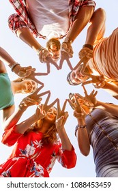 group of five cheerful friends building star shape with their fingers to express their friendship. students after college symbolize their togetherness and team work with a figure. captured from below