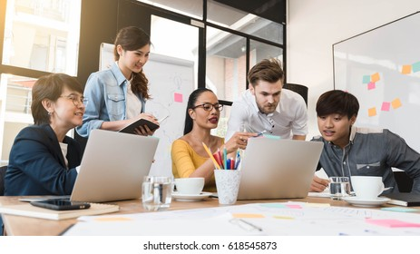 5人のクリエイティブワーカーのグループがオフィスでブレインストームし、新しいスタイルのワークスペース