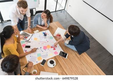 5人のクリエイティブワーカーのグループがオフィスでブレインストーム、新しいスタイルのワークスペース、オフィスの人々の幸せなシーン(コピースペース)