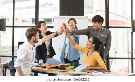 Group of five creative workers giving each other high-five with big smile on face, successful team performance, finishing touch