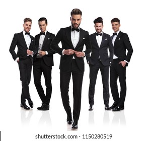 group of five elegant men wearing black tuxedoes with leader buttoning suit and stepping in front of them, full body picture