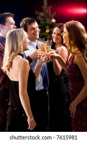 Group of five friends clinking  glasses with each other at christmas