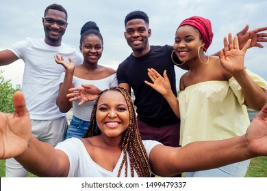 group of five friends female and male taking selfie on camera smartphone and having fun outdoors lifestyle near lake