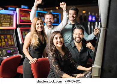 Group of five friends having a good time together while they play some slots in a casino and they win some money