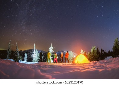 Group of five friends with tent is enjoying beautiful night landscape against mountains, stars and milky way