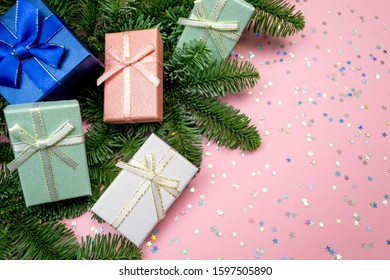 Group of five gift boxes with ribbon, christmas tree branch border and rainbow holographic stars confetti. Flat lay on pink pastel background with copy space mock up. Top view close up clipart concept