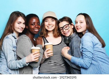 Group of five girls friends of different nationalities holding a cup of coffee