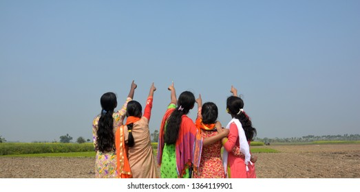 A group of five girls pointing towards the sky in a field wearing salwar kameez, selective focusing.