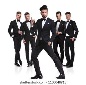 group of five groomsmen with leader snapping fingers in front and looking to side, while standing on white background, full body picture