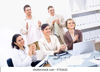 Group of five happy business people smiling and clapping, looking at same direction.