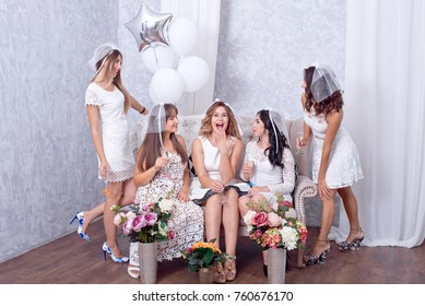 Group of five happy elegant young women friends celebrating together toasting with flutes of champagne as they laugh together standing in a line in a white themed image.