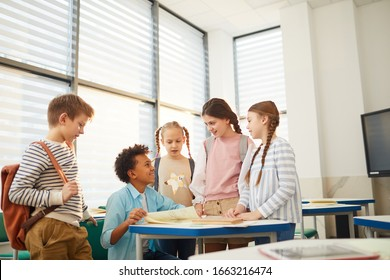 Group of five happy friends chatting about something funny during break time at school, copy space