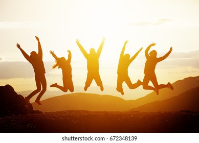 Group of five happy friends jumps at sunset time on background mountains