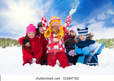 Group of five happy kids, boys and girls throw snow in the air