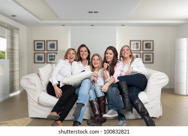 A group of five happy women of different ages laughing in the living room