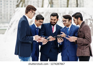 Group of five indian businessman in suits posed outdoor in winter day at Europe, looking on phones and disscus.