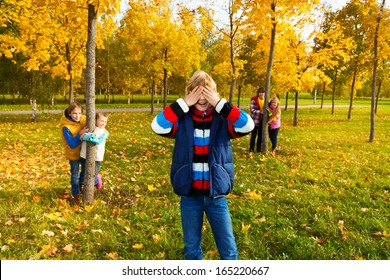 Group of five kids play hide and seek with boy counting and friends hiding behind the trees