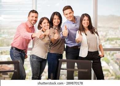 Group of five Latin people in casual attire giving their thumbs up and smiling