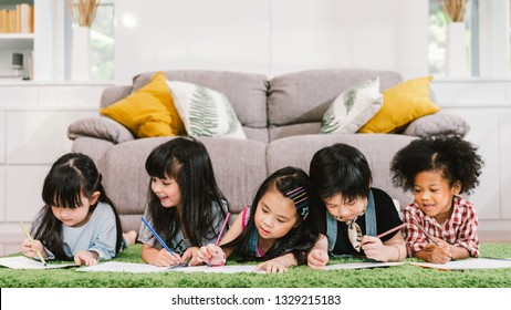 Group of five multi-ethnic young cute preschool kids, boy and girls happy studying or drawing together at home or school. Children education, youth culture lifestyle, or fun learning activity concept