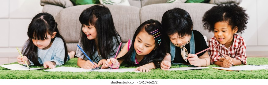Group of five multi-ethnic young cute preschool kids, boy and girls happy study or drawing together at home or school. Children education, youth culture, or fun learning activity concept. Banner size