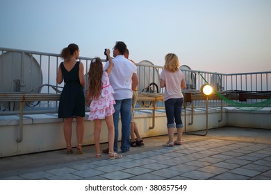 A group of five people with binoculars on the roof of a multistory building against the sky, view from the back