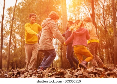 Group of a five people having fun in the autumn park.