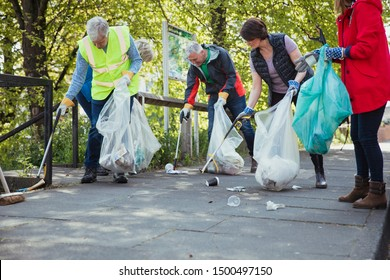 A group of five people participating in a city clean-up together.
