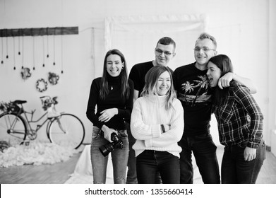 Group of five peoples, friends photographers and designers on studio shooting after hard work day. They happy and laughing.
