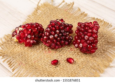 Group of five pieces of fresh red pomegranate on natural sackcloth on white wood