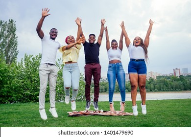 group of five smiling african-american men and women walking outside cloudy weather near the lake,exchange students in Russia team work