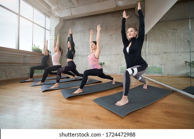 Group of five smiling girls practicing yoga in fitness hall. Young fit women stretching with hands up on mats in gym with big windows and mirror, loft interior. Concept of healthy lifestyle.