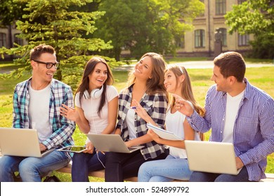 group of five smiling happy beautiful classmates sitting on bench and talk with each other.