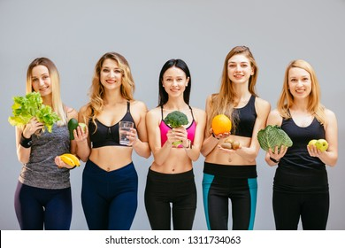 Group of five smiling positive sports people with vegetables and fruits over grey backgound. Team of slim fitness women in sportswear show healthy food cholesterol diet concept.