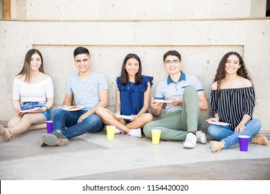Group of five teenage boys and girls sitting outside in sidewalk eating pizza